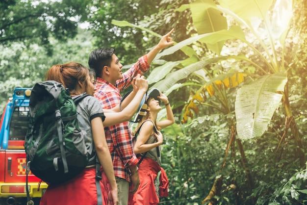 Paar of vrienden die samen glimlachend gelukkig tijdens het kamperen reisreis in openlucht in bos navigeren