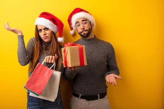 Paar of vrienden houden geschenken en boodschappentassen verward en twijfelachtig