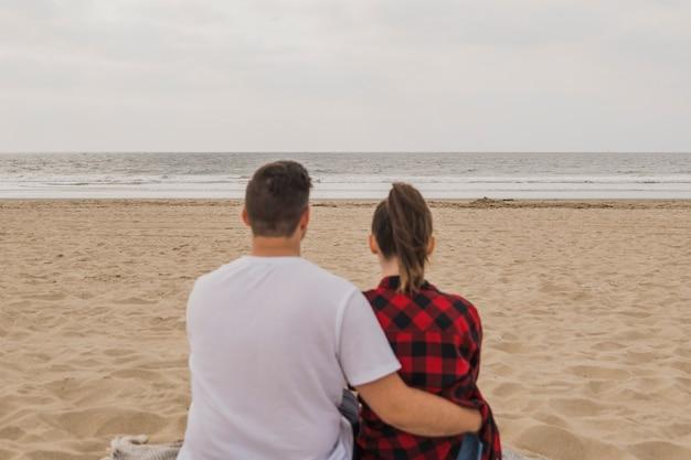 Paar omarmd op strand