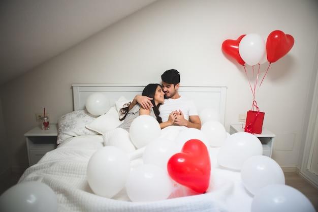 Paar omarmen in bed, omringd door ballonnen