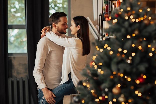 Paar omarmen in de buurt van kerstboom.