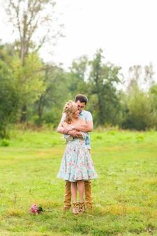 Paar omarmen op het platteland. jonge romantische man en vrouw staan en knuffelen elkaar met tederheid op de natuur.