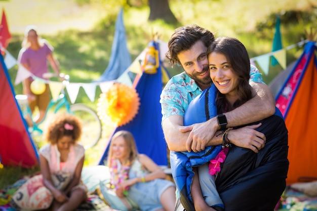 Paar omhelzen elkaar op de camping