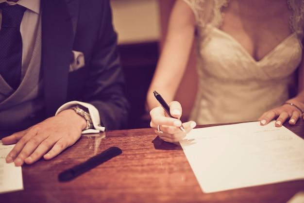 Paar ondertekening van hun trouwdag in detail geschoten met selectieve focus en vintage toon.