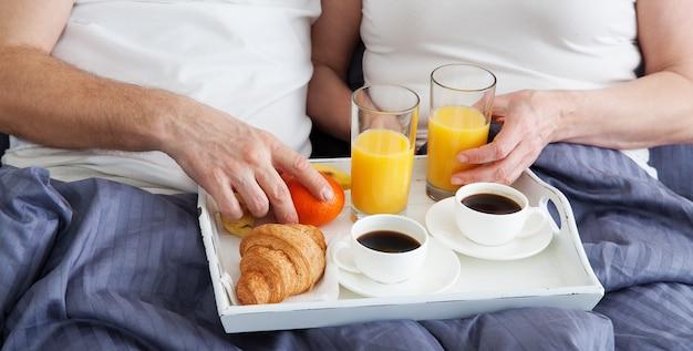 Paar ontspannen in bed met een kopje koffie