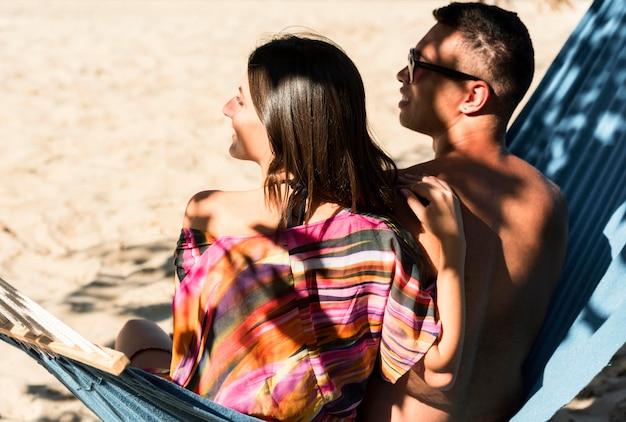 Paar ontspannen in hangmat terwijl op het strand