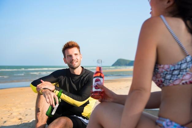 Paar ontspannen met bier op het strand