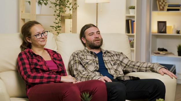 Paar ontspannen op de bank en praten met elkaar terwijl u tv kijkt.