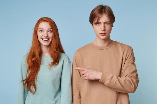 Paar op blauw. de vrouw glimlacht en de man wijst naar haar