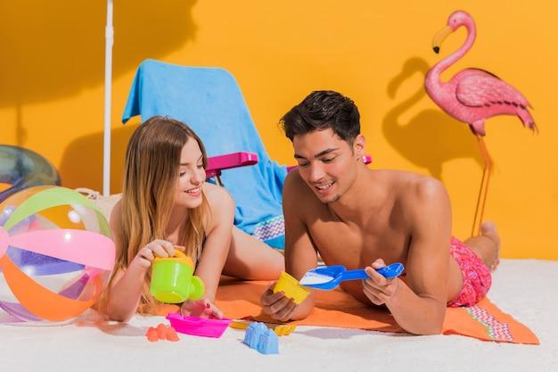 Paar op het strand spelen met speelgoed