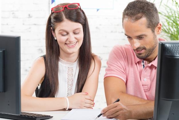 Paar op het werk op kantoor, man schrijven