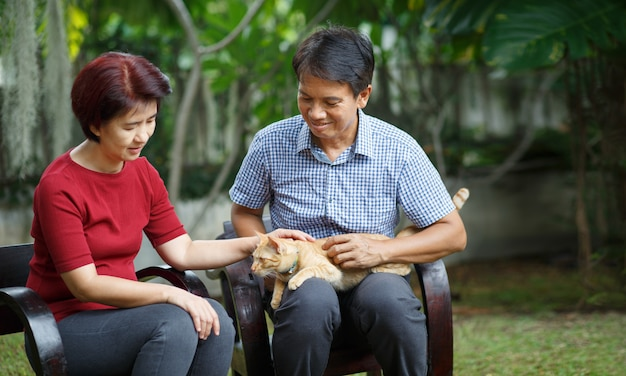 Paar op middelbare leeftijd ontspant zitting op bank met kat in binnenplaats