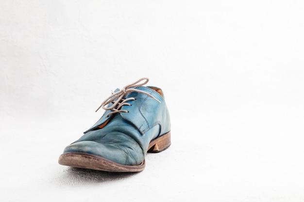 Paar oude leren blauwe afgedankte laarzen met veters
