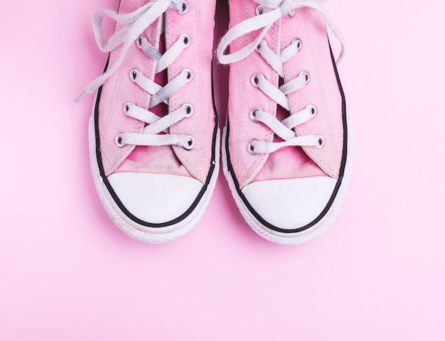 Paar oude versleten roze sneakers met witte veters