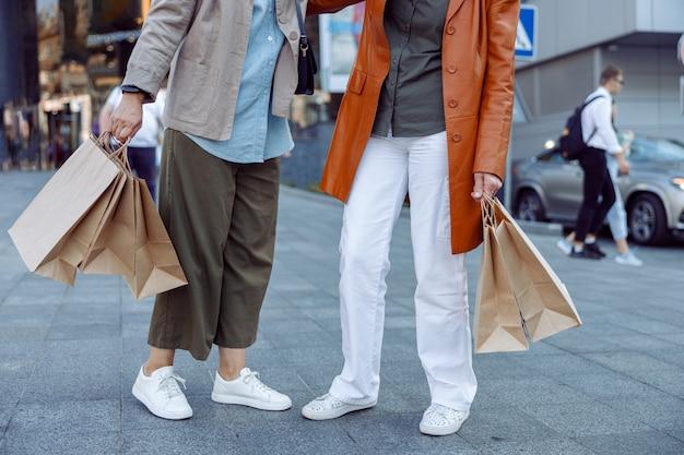 Paar oudere dames houden boodschappentassen vast die op de moderne stadsstraat staan