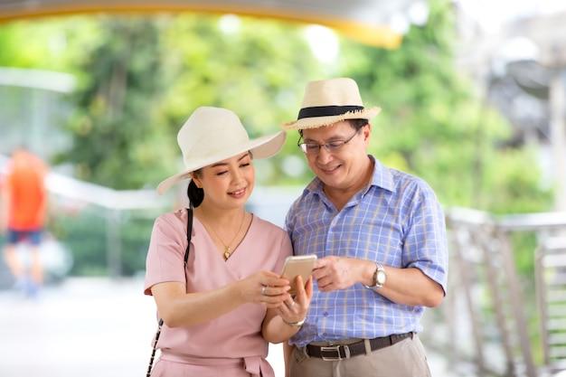 Paar ouderen met hoed staande op buiten kijken op mobiele telefoon.