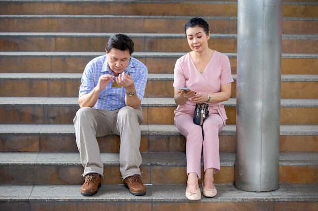 Paar ouderen zittend op trap buiten kijken op mobiele telefoon.
