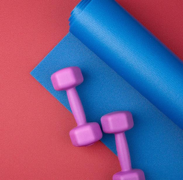 Paar paarse plastic dumbbells en blauwe neopreen mat