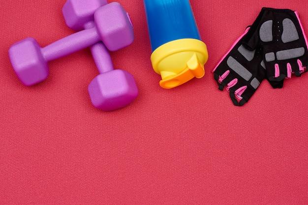 Paar paarse plastic halter, handschoenen en een blauwe fles water voor sport