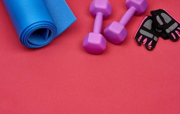 Paar paarse plastic halter, handschoenen en een blauwe sportmat op een rood