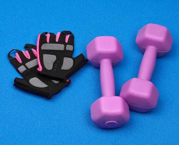 Paar paarse plastic halters, handschoenen op een blauwe neopreen mat