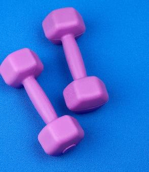 Paar paarse plastic halters op een blauwe neopreen mat