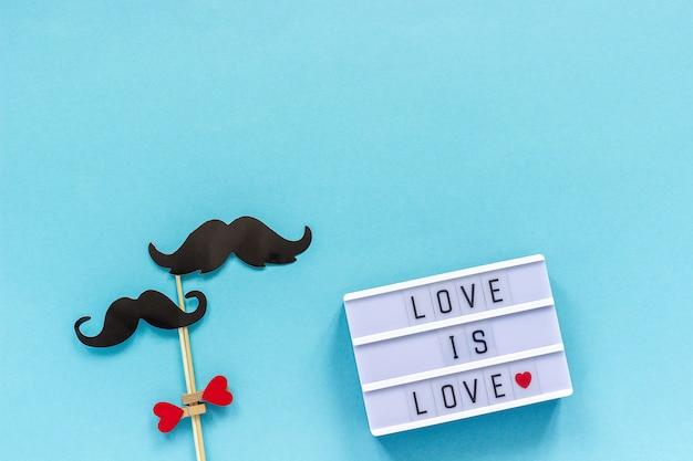 Paar papier snor rekwisieten op stok en lichtbak met tekst liefde is liefde op blauwe achtergrond