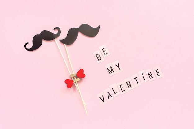 Paar papieren snor rekwisieten op stick vastgemaakt wasknijper hart en tekst be my valentine