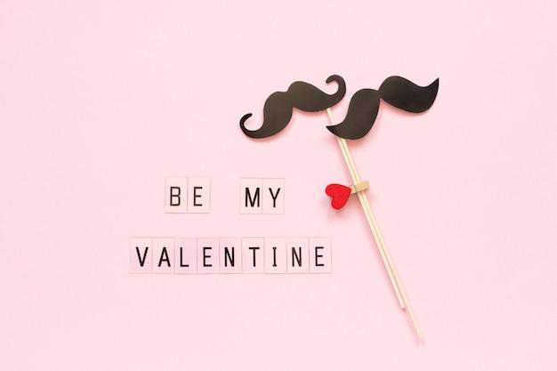 Paar papieren snor rekwisieten op stok en tekst wees mijn valentijn op roze