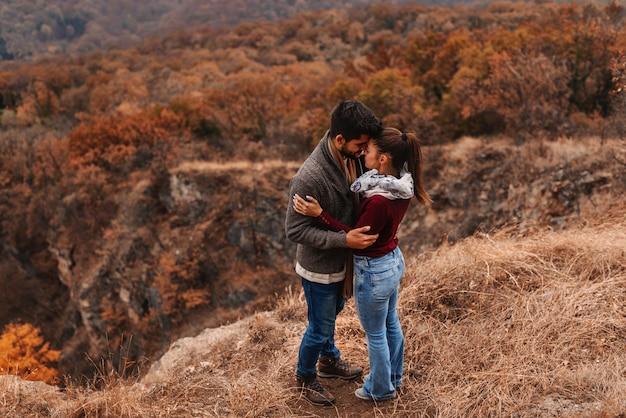 Paar permanent op gezichtspunt en kussen. in achtergrond bos, herfst tijd.
