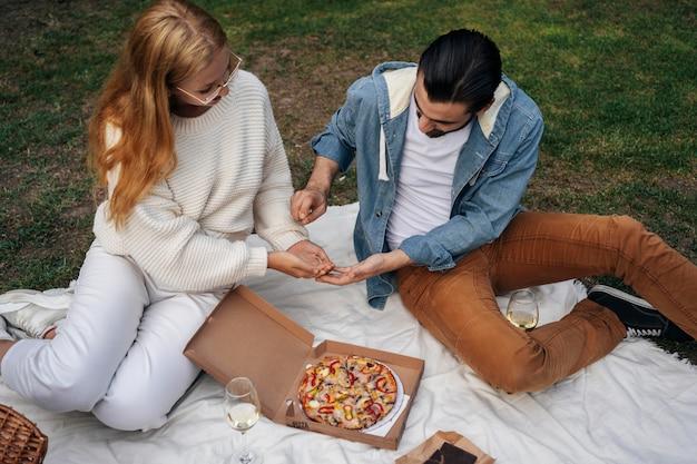 Paar pizza buiten eten