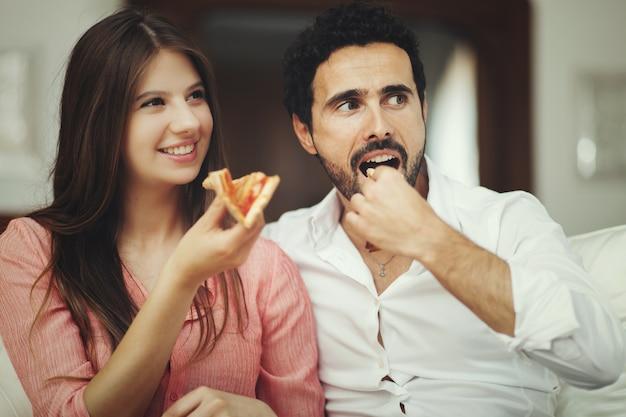 Paar pizza eten en tv kijken