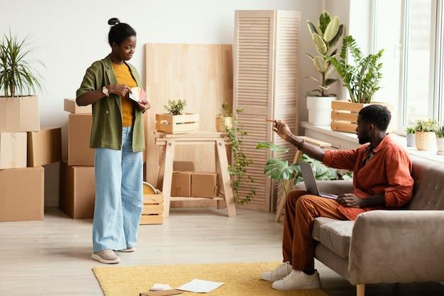 Paar plannen maken voor het renoveren van huis met behulp van laptop en kleurenpalet