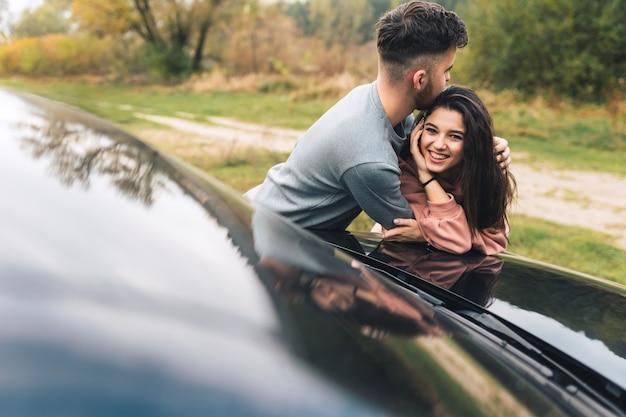 Paar plezier gek rond in de buurt van auto