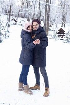 Paar plezier houden schittert in winter park met sneeuw