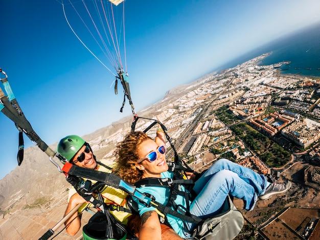 Paar plezier in de lucht paragliden over de stad met uitzicht op de kustlijn