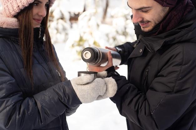 Paar plezier terwijl het gieten van thee uit een thermoskan in winter park