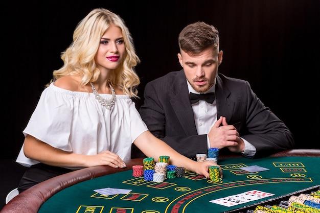 Paar pokeren aan de groene tafel. het blonde meisje en een man in een pak. chips inzetten