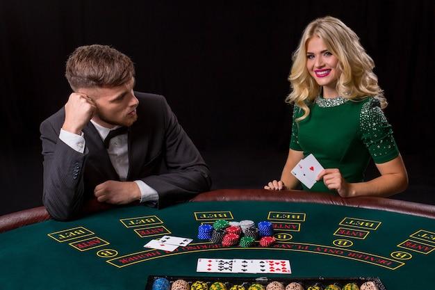 Paar pokeren aan de groene tafel. het blonde meisje en een man in een pak. gelukkige overwinning, twee azen
