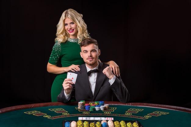 Paar pokeren aan de groene tafel. het blonde meisje en een man in een pak. gelukkige overwinning, twee