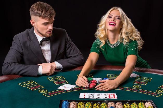 Paar pokeren aan de groene tafel. het blonde meisje en een man in een pak. gelukkige overwinning