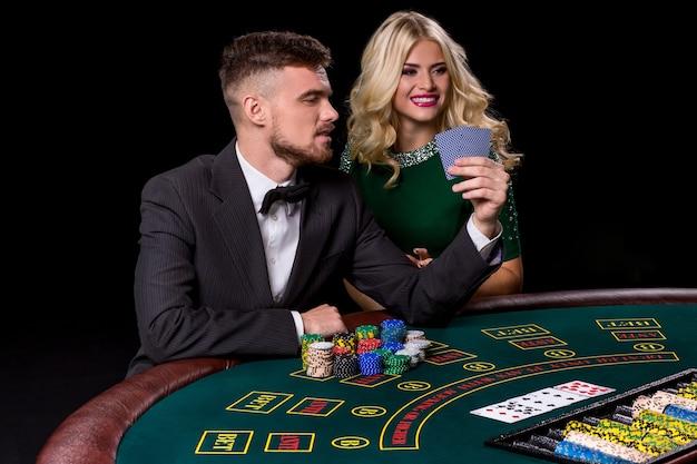 Paar pokeren aan de groene tafel. het blonde meisje en een man in een pak.