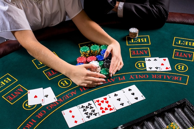 Paar pokeren aan tafel. het blonde meisje en een man in een pak. close-up handen. neem chips gewonnen