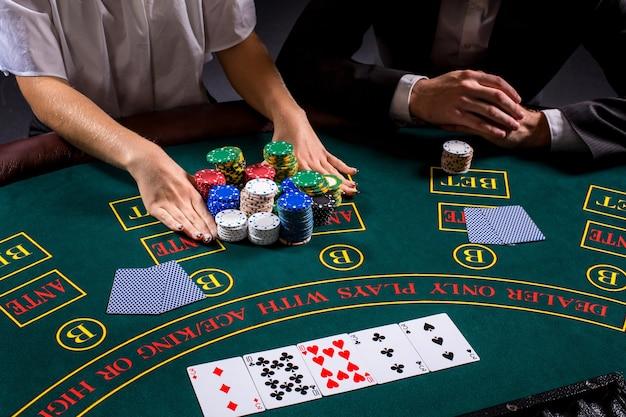 Paar pokeren aan tafel. het blonde meisje en een man in een pak. close-up handen. weddenschappen all-in