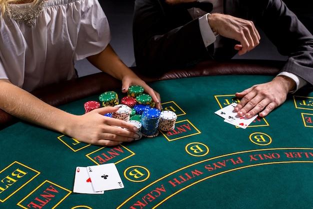 Paar pokeren aan tafel. het blonde meisje en een man in een pak. close-up handen.