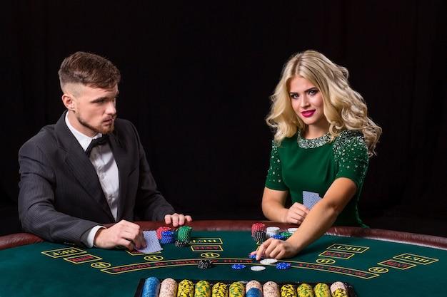 Paar pokeren aan tafel. het blonde meisje en een man in een pak. vrouw zet chips in