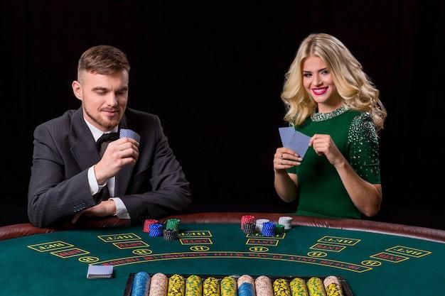 Paar pokeren aan tafel. het blonde meisje en een man in een pak.
