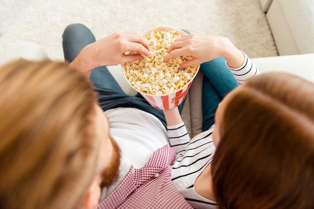 Paar popcorn eten op de bank thuis en tv kijken
