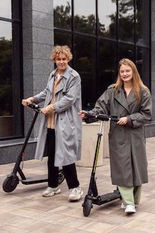Paar poseren met elektrische scooters buitenshuis