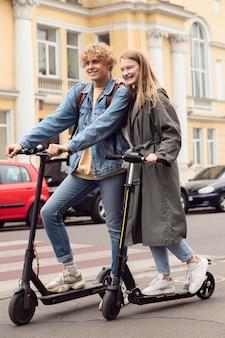 Paar poseren samen buiten op elektrische scooters